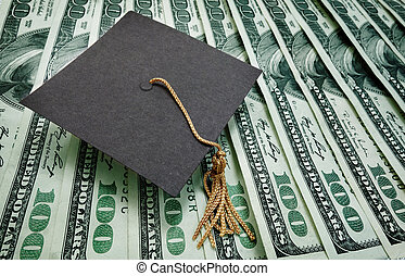 education money - graduation cap on assorted hundred dollar...