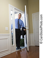 Businessman coming home. - Caucasian businessman at open...