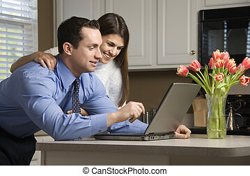 Couple with laptop. - Caucasian couple in kitchen looking at...