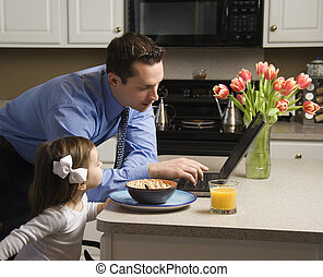 Man with child - Caucasian father in suit using laptop...