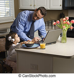 Father with daughter - Caucasian father in suit using laptop...