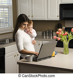 Mother with baby - Caucasian woman holding baby and typing...