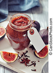 Fig jam in a glass jar with fresh figs on wooden background