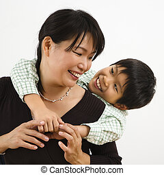 Son hugging mother - Asian mother with young son hugging her...