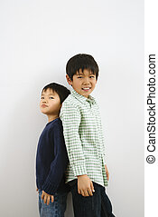 Brothers back to back - Two young Asian brothers standing...