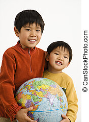 Boys holding globe - Two Asian boys holding world globe and...