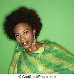 Portrait of woman with afro wearing green striped shawl on...