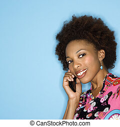 Smiling woman on cellphone - Woman with afro wearing vintage...