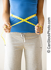 Measuring waist - Woman standing pulling measuring tape...
