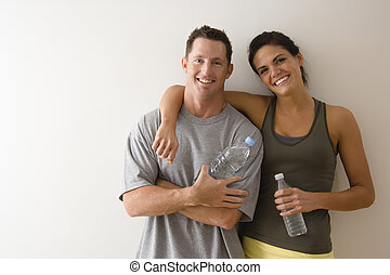 Fitness couple - Man and woman at gym in fitness attire...