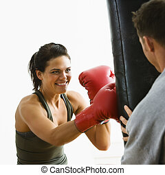 Woman fitness training - Woman wearing boxing gloves hitting...