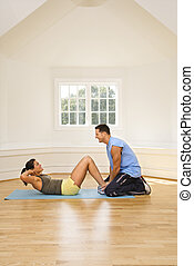 Woman doing sit ups - Man holding womans feet down as she...