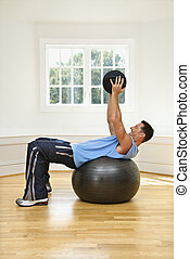 Strength training - Man lifting medicine ball while on...