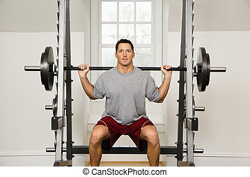 Man lifting weights in gym.