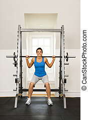 Woman lifting weights in gym smiling.