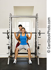Woman lifting weights in gym being assisted by man.