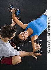 Woman lifting weights - Man assisting woman lifting weights...