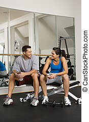 Socializing at gym - Man and woman sitting on exercise...