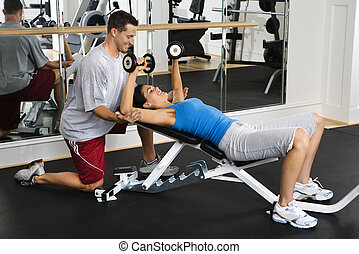 Woman doing workout - Man assisting woman at gym with hand...