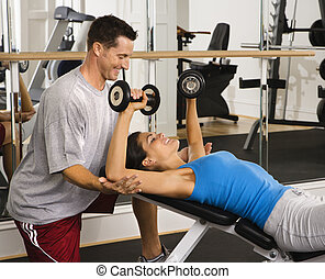 Training at gym - Man assisting woman at gym with hand...