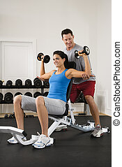 Gym workout - Man assisting woman at gym with hand weights...