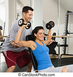 Woman lifting weights - Man assisting woman at gym with hand...