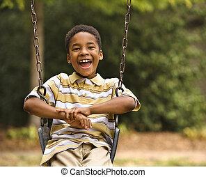 Boy on swing - Happy smiling boy on swing in park...