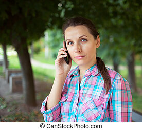 Portrait of a woman in a park talking on the phone