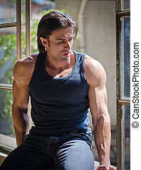 Handsome, muscular man sitting on open window - Attractive,...