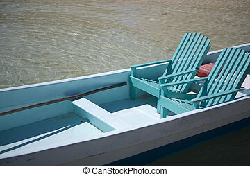 Two chairs in a small boat near the shore - Two wooden...
