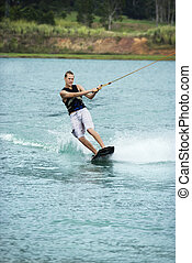 Teen wakeboarder - Caucasian young adult male wakeboarding...