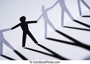 Minority - One black cutout paper person holding hands with...