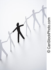 People holding hands - One black cutout paper person holding...