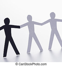 Racial unity - Black and white cutout paper people holding...