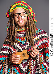 dreadlocks man - Portrait of a hippie young man playing his...