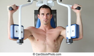 Bare Chest Exercises - Topless adult male uses a chest...