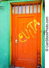 Orange Door and Green Wall - An orange door with graffiti...
