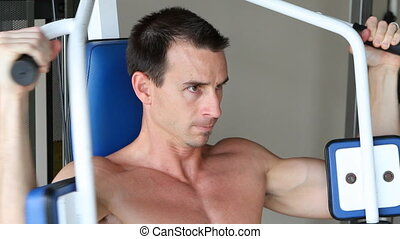 Bare Chest Exercising - Adult man uses home gym equipment to...