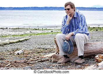 Depressed man sitting on driftwood on beach - Depressed, sad...