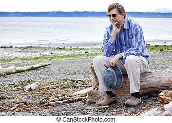 Depressed man sitting on driftwood on beach - Depressed, sad...