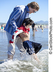 Father helping disabled son walk in the ocean waves on beach...