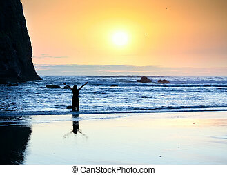 Girl standing in waves, arms raised to sky at sunset -...