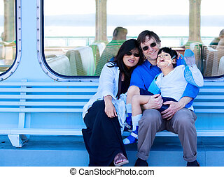 Interracial couple holding disabled son on ferry boat deck -...