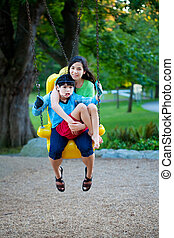 Big sister holding disabled brother on special needs swing...