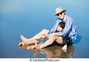 Father playing with disabled son on beach, holding him...