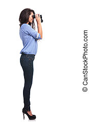 side of a casual woman looking through binoculars