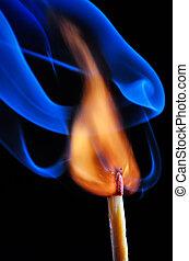 Burning match with blue smoke on black background