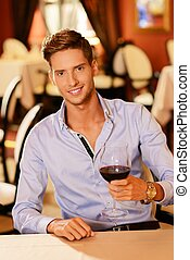 Handsome young man with glass of red wine in restaurant