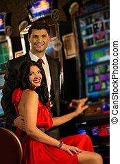 Beautiful young couple near slot machine in a casino