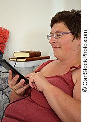 Frau mit ihrem eBook - Frau handiert am Touchscreen des...